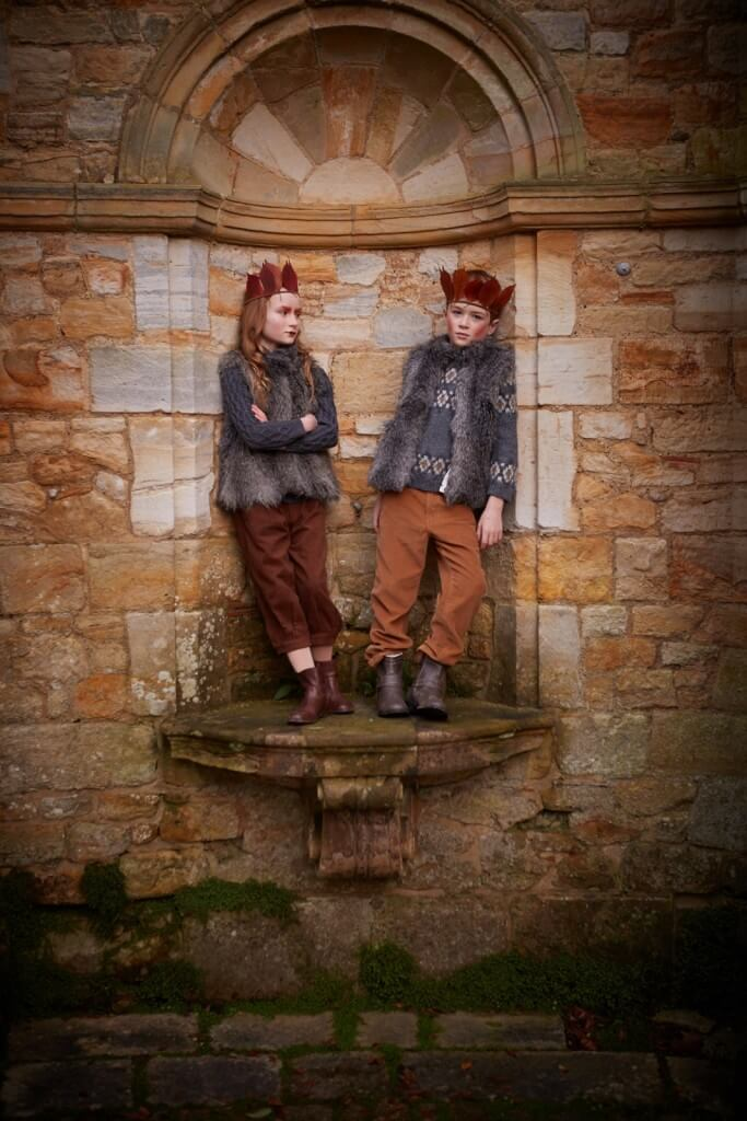 Girl wears sweater and breeches by Rachel Riley. Boy wears sweater and trousers by Bon Point. Both wear faux fue gilets by Angel & Rocket. Crowns hand made by Stylist