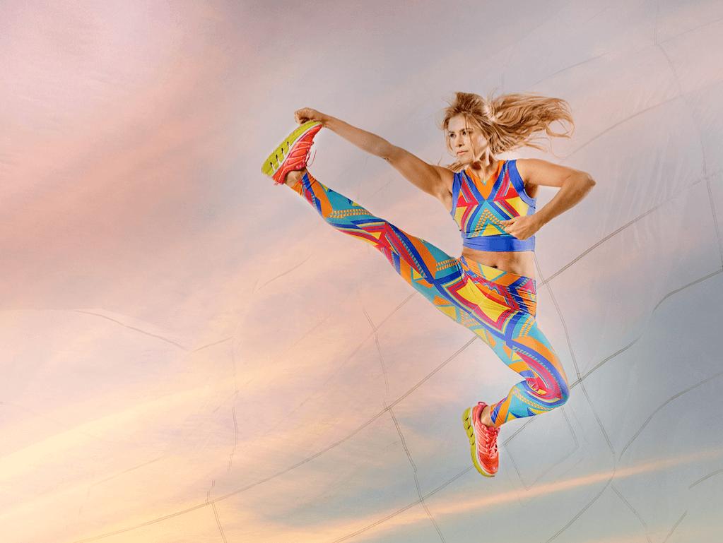 Tara wears geometric print top and leggings by Sarah & Sorrentino at Style Sportif. Trainers by Hoka One One.